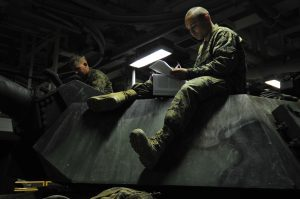 U.S. Marine Corps Pfc. Benjamin Couse, right, sits atop an M1A1 Abrams tank while studying math aboard the amphibious assault ship USS Makin Island (LHD 8) in the Pacific Ocean off the coast of Southern California Feb. 25, 2011. Makin Island is participating in exercise Iron Fist, a three-week bilateral training event held annually between the U.S. Marine Corps and the Japan Ground Self-Defense Force designed to increase interoperability between the two services while aiding the Japanese in their continued development of amphibious capabilities. Couse is assigned to Charlie Company, 1st Tank Battalion. (U.S. Navy photo by Chief Mass Communication Specialist John Lill/Released)